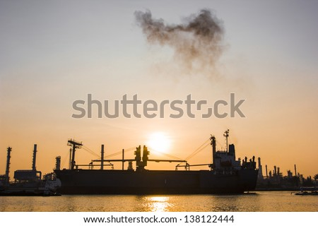 Oil refinery view and freighter with Sunrise
