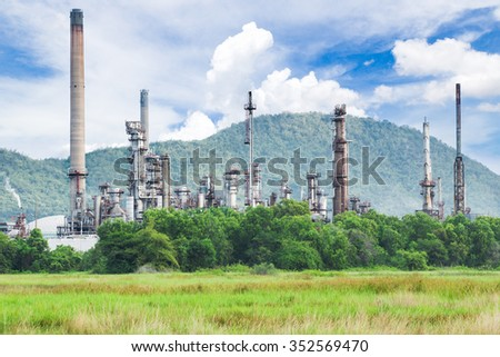 Oil refinery with green grass field - stock photo