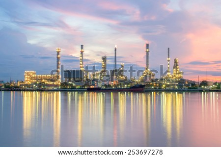 Oil refinery with reflection, petrochemical plant at sunrise