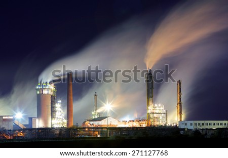 Oil refinery with vapor - petrochemical industry at night - stock photo