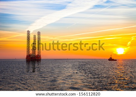 Oil rig at sunset background. - stock photo