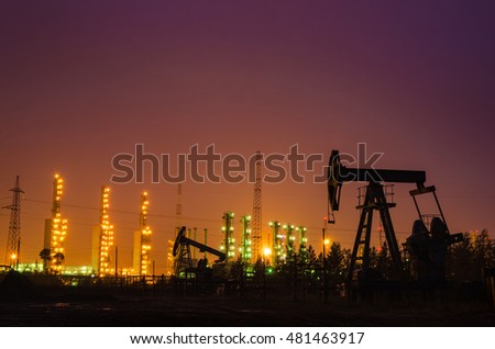 Oil rig at the background of refinery by night. Oil and gas industry. Toned.