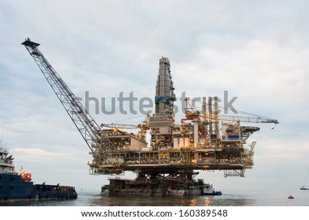 Oil rig being tugged in the sea - stock photo
