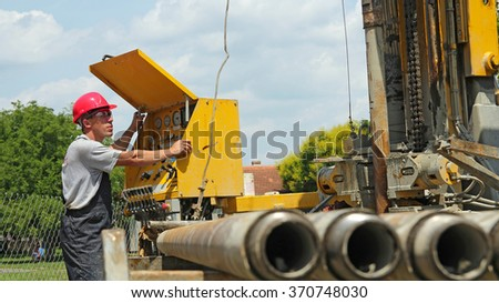 Oil Rig Machine Operator Using Control Panel. Oil and Gas Industry. Oil and gas well drilling worker operates drilling rig machinery. - stock photo