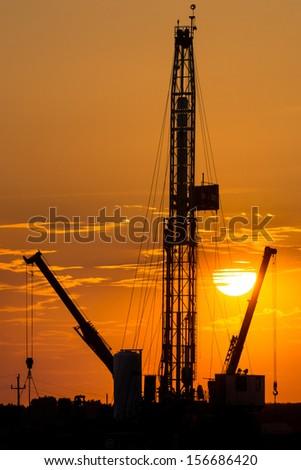 Oil rig on orange sunset - stock photo