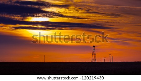 Oil rig profiled on beautiful evening sky - stock photo
