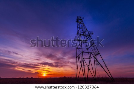 Oil rig profiled on dramatic sunset sky - stock photo