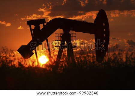 Oil rig pump jack silhouetted by setting sun