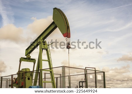 oil rig pumping on cloudy sky background - stock photo