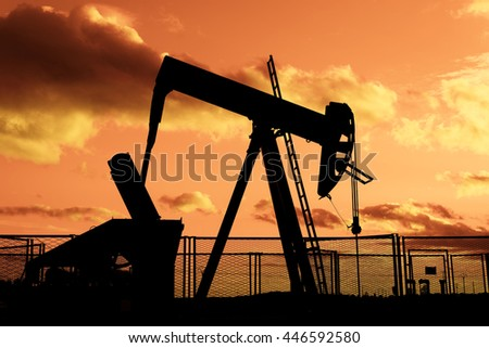 oil rig pumping on cloudy sky background at dusk - stock photo