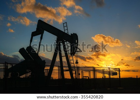 oil rig silhouette pumping at evening on cloudy sky background - stock photo