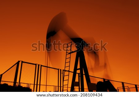 oil rig silhouetteworking at sunset lighting - stock photo