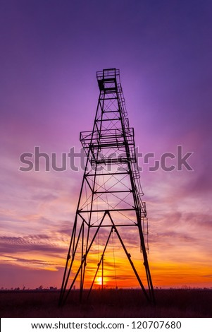 Oil rig structure profiled on warm and beautiful sunset colors - stock photo