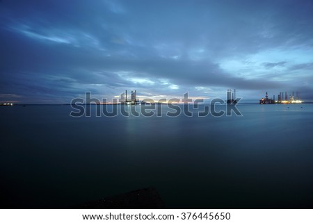 Oil rig with blue hour and formation of cloudscape. Bad weather, oil and gas environment - stock photo