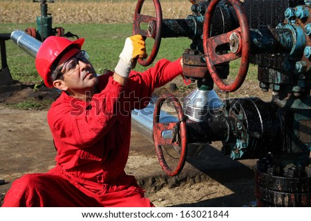 Oil Rig Worker. Oil and gas industry.  Oil worker turning valve on oil rig.  - stock photo