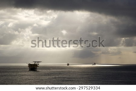 Oil rigs and rainclouds in the midst of an open sea - stock photo