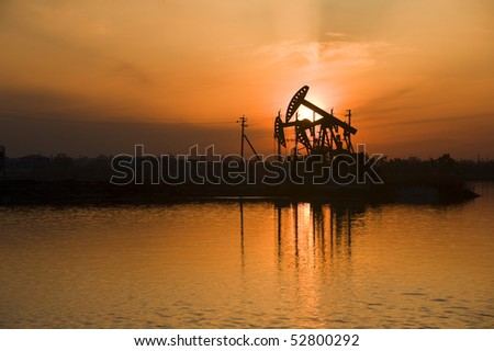 Oil rigs silhouette over orange sky-5 - stock photo