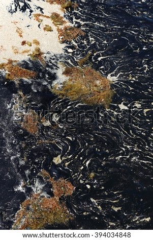 Oil Spill: old oil spill now solidified and still contaminating beach years later - stock photo