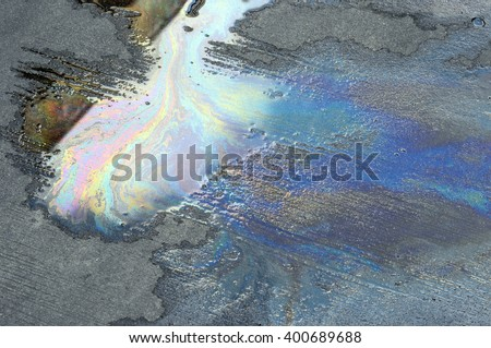 Oil spill on asphalt road background or texture