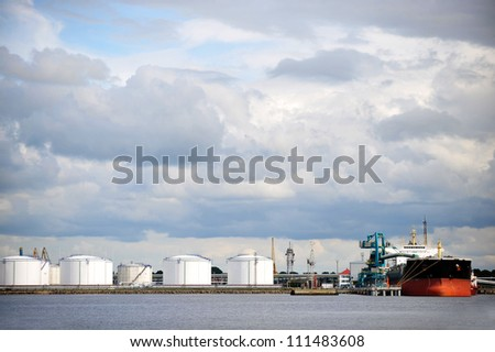 Oil Storage tanks at harbor under cloudy sky - stock photo
