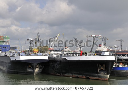 oil tanker and cargo ship in the port of rotterdam netherlands - stock photo