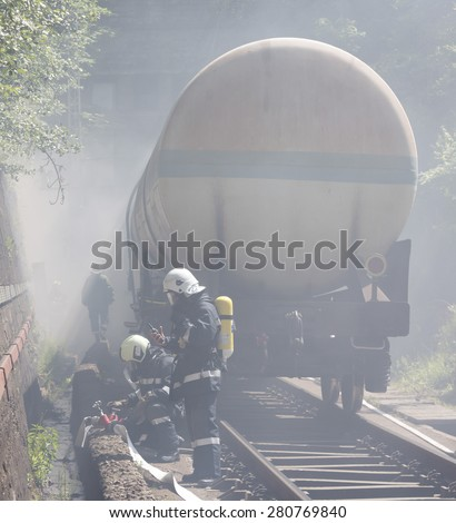 Oil tanker train is seen in smoke near Sofia, Bulgaria. Fire safety and civil protection service at Fire department is training in a situation of train crash with spilled toxic and flammable materials - stock photo