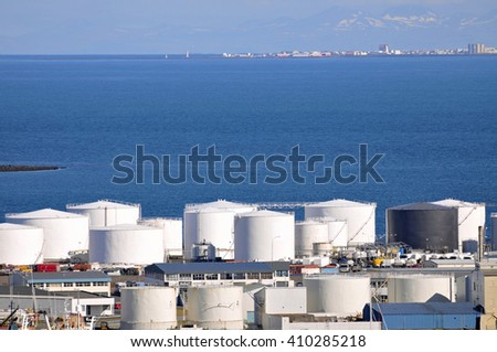 Oil tanks on seashore, with blue copy-space - stock photo