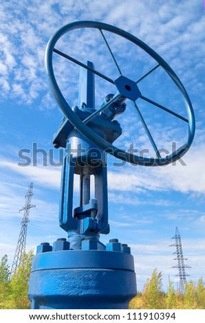 Oil valve with power masts in the background - stock photo