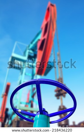 Oil valve with rocking in the background - stock photo