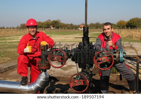 Oil Well and Two Oil Workers. Oil and Gas Industry. Oil worker and oil engineer giving thumb up sign. Teamwork. - stock photo