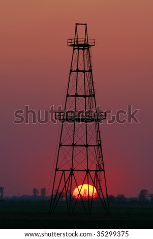 Oil well profiled on solar disc at sunset