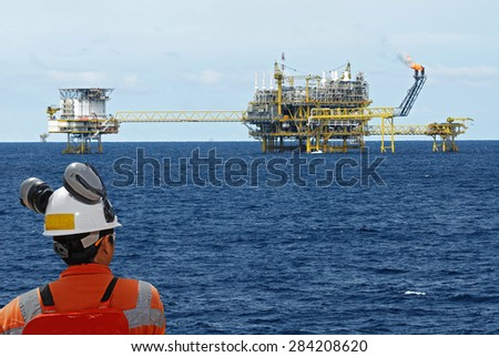 oil worker and oil rig - stock photo