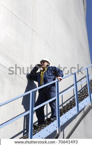 oil worker, engineer standing on stairs alongside fuel storage tower, - stock photo