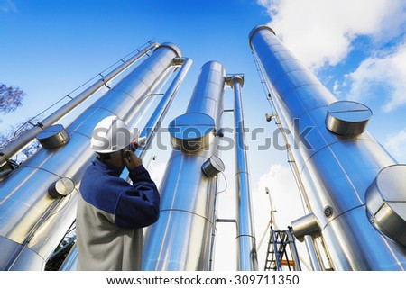 oil-worker, engineer with large oil and gas pipes, pipelines, slight HDR effects. - stock photo