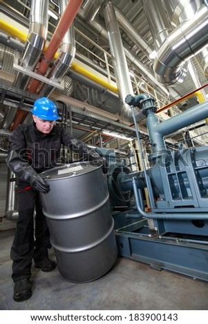 Oil Worker in coveralls,hardhat and rubber gloves dealing with silver oil barrel