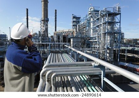 oil-worker in foreground pointing at oil and gas refinery in background - stock photo