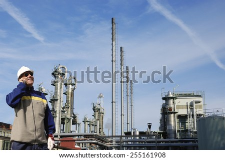 oil worker in front of large oil and gas refinery - stock photo