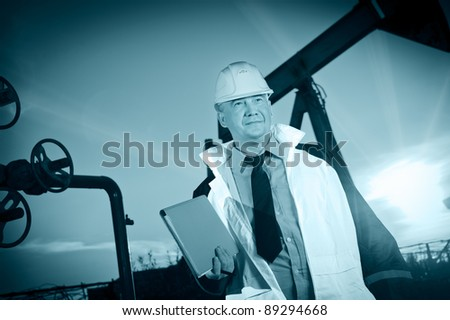 Oil worker in uniform and helmet on of background the pump jack and sunset sky. Toned. - stock photo