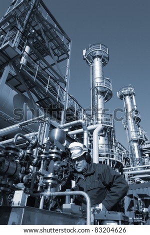 oil worker inside oil and gas refinery, blue toning idea - stock photo