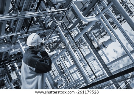 oil worker pointing at giant pipelines construction inside refinery details - stock photo