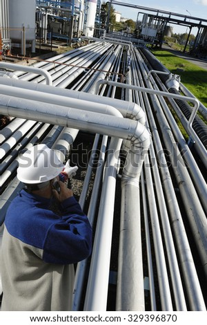 oil worker pointing out on long stretched pipelines inside refinery industry - stock photo