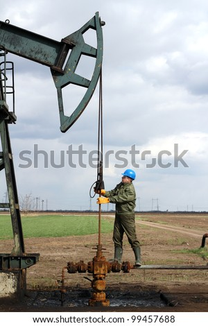 oil worker standing at pipeline - stock photo