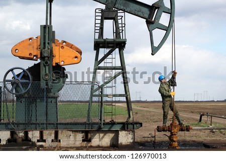 oil worker standing at pipeline and check pump jack