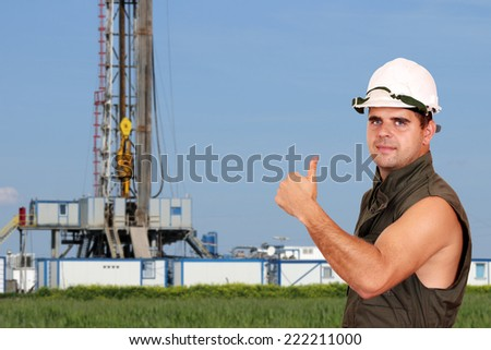 oil worker thumb up and land drilling rig - stock photo