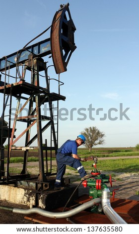 oil worker with pipe wrench and pipeline - stock photo