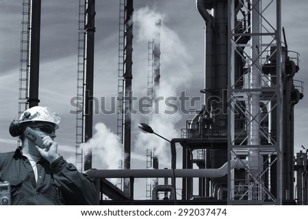 oil worker with refinery, smoke and smog - stock photo
