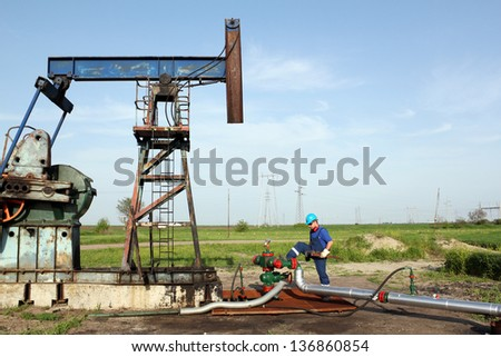 oil worker with wrench on oil field - stock photo
