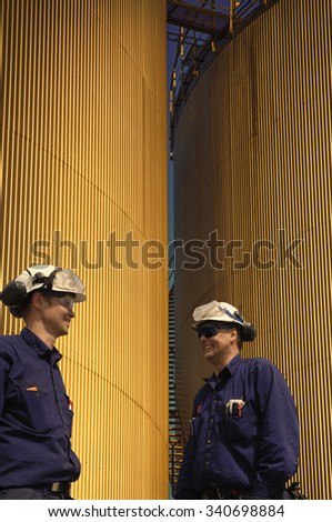 oil workers and storage tanks at sunset time - stock photo