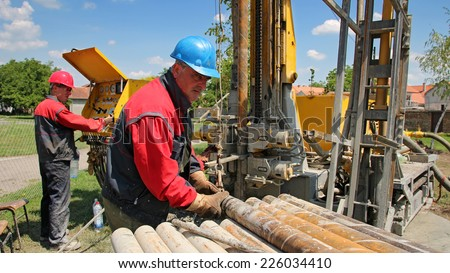 Oil Workers at Work. Oil and gas industry. Oil drilling rig workers lifting drill pipe. Power and energy. - stock photo