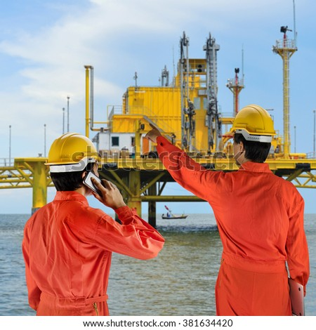 Oil workers in orange uniform and helmet on of rig background  - stock photo